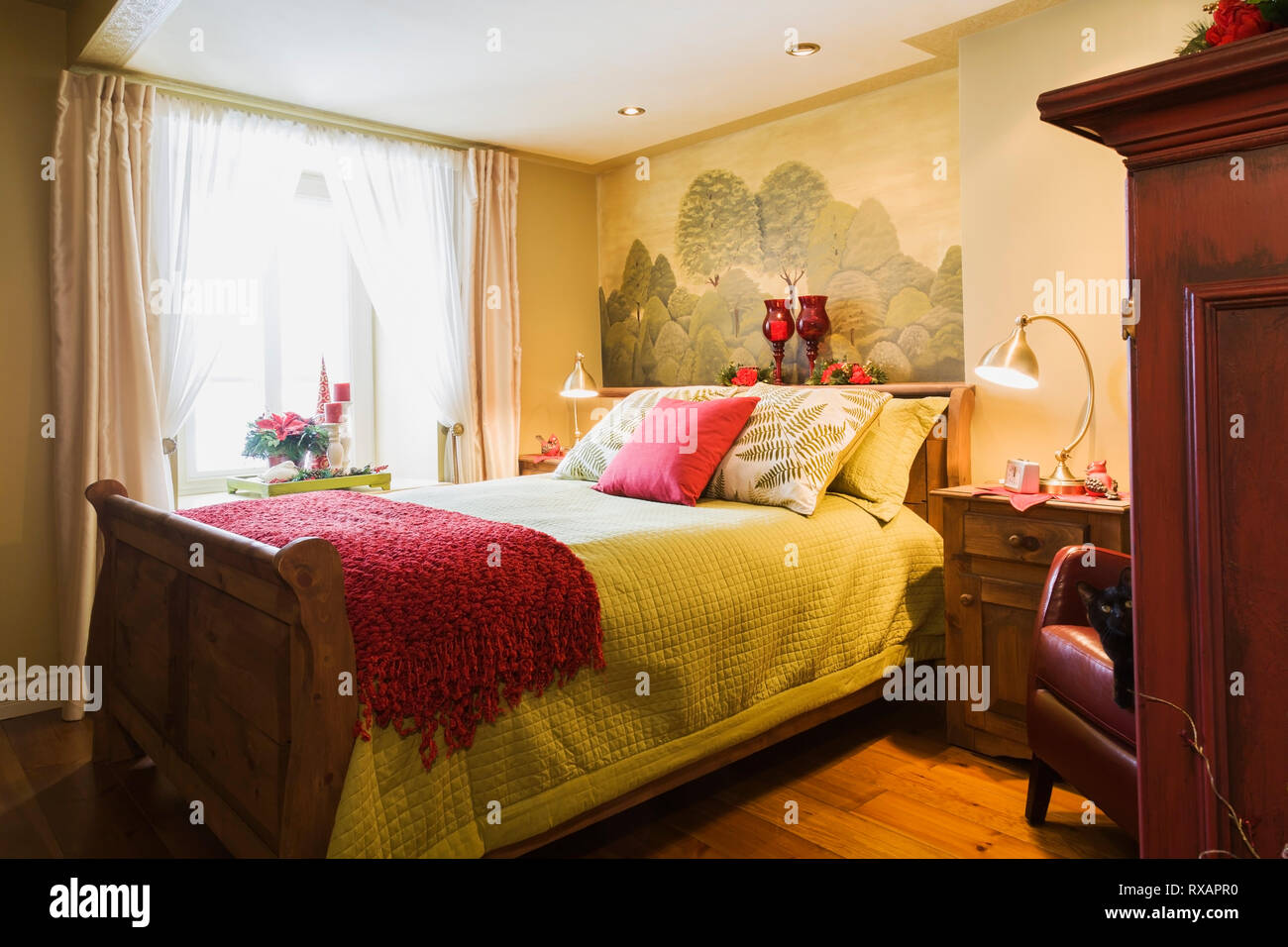 Queen size wooden sleigh bed in guest bedroom on the groung floor inside an old (circa 1840) Canadiana cottage style home, Quebec, Canada. This image  - Stock Image