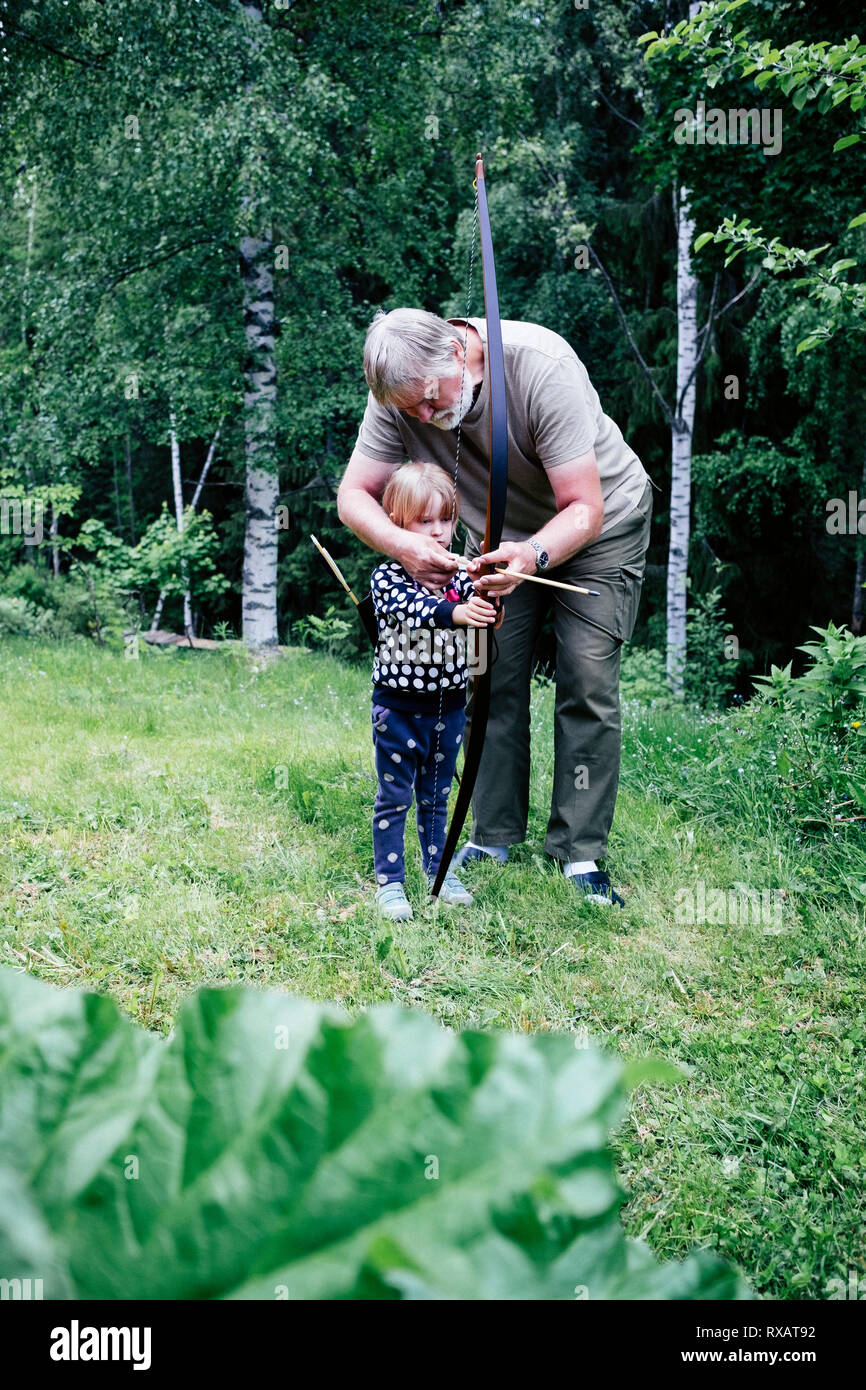 Grandfather guiding granddaughter in aiming arrow while standing on grassy field at forest - Stock Image