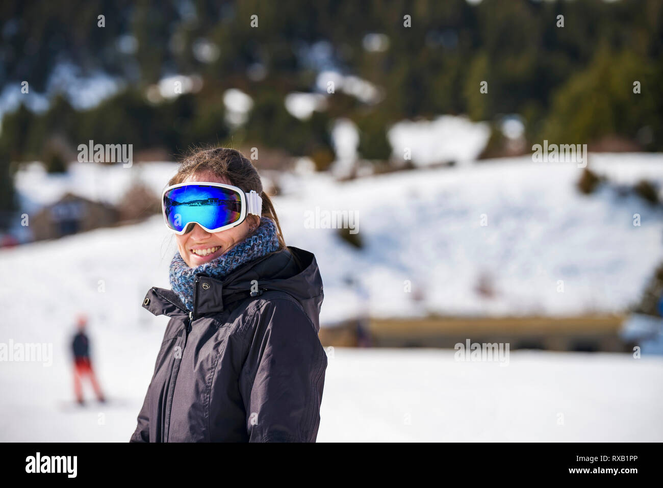 Portrait of smiling woman wearing ski goggles while standing on snow covered field - Stock Image