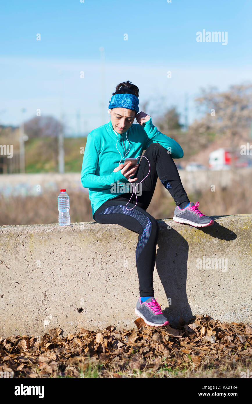 Female athlete using smart phone while sitting on retaining wall against sky at park during sunny day - Stock Image