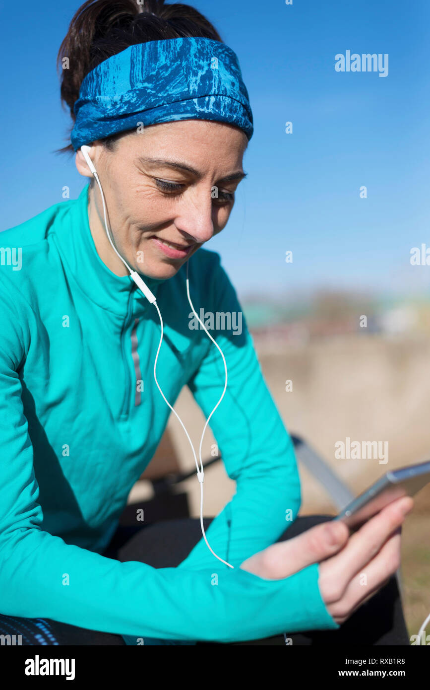 Female athlete using smart phone while sitting against blue sky at park during sunny day - Stock Image