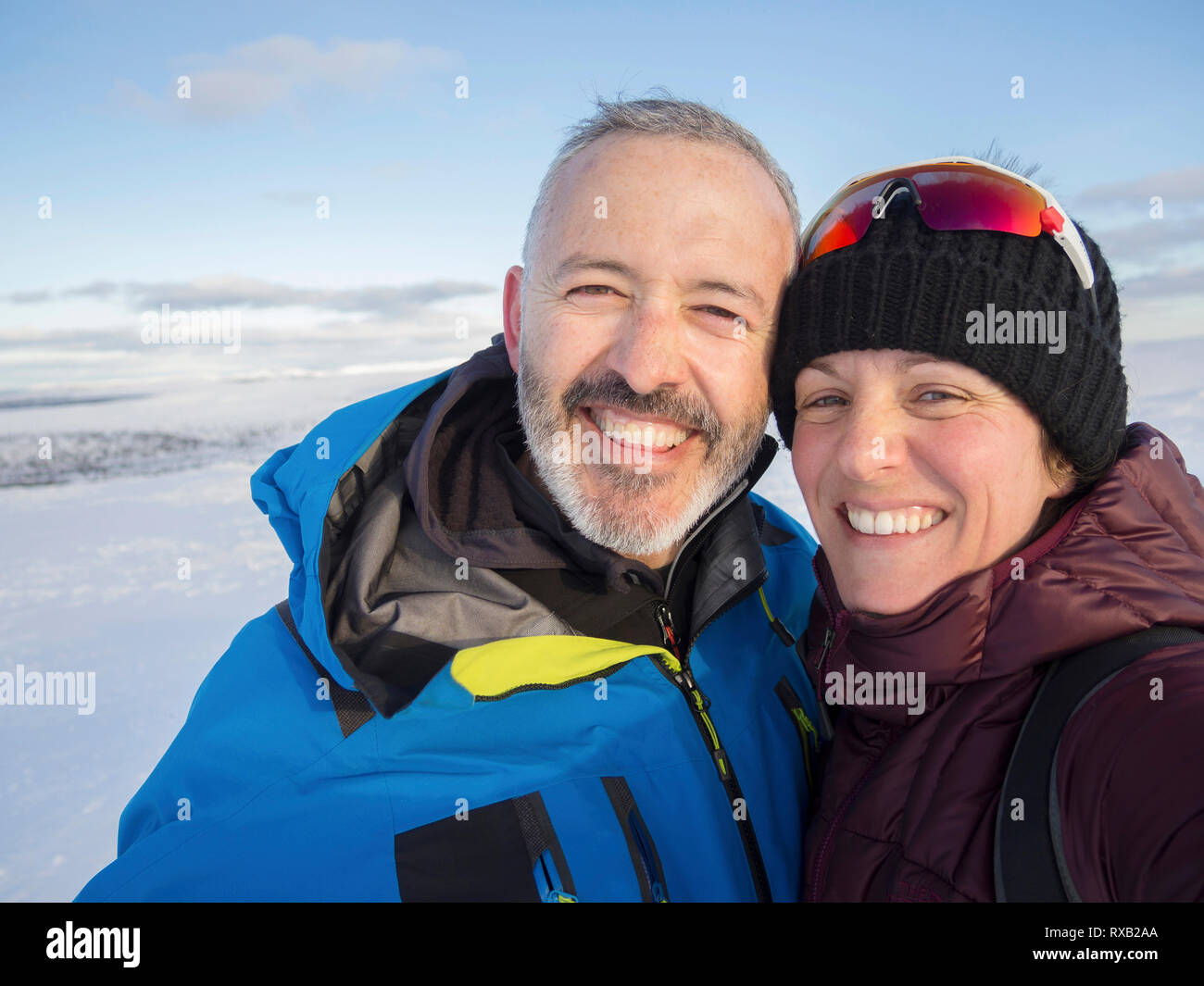 Portrait of happy couple standing on snow covered landscape against sky during sunset Stock Photo
