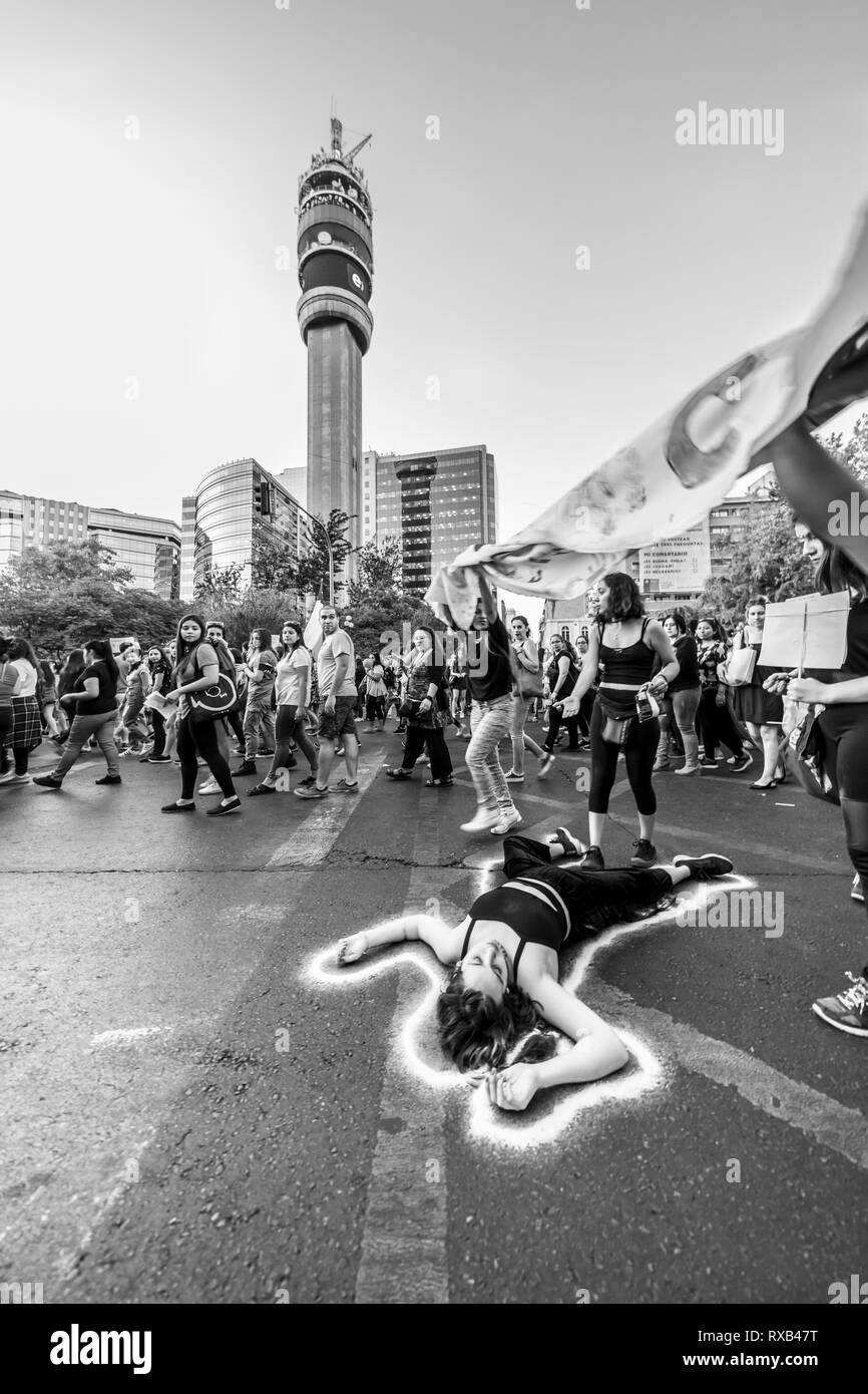 Girl protester lying on the street asphalt at International Women's Day 8 March at Santiago city centre streets, Chile - Stock Image