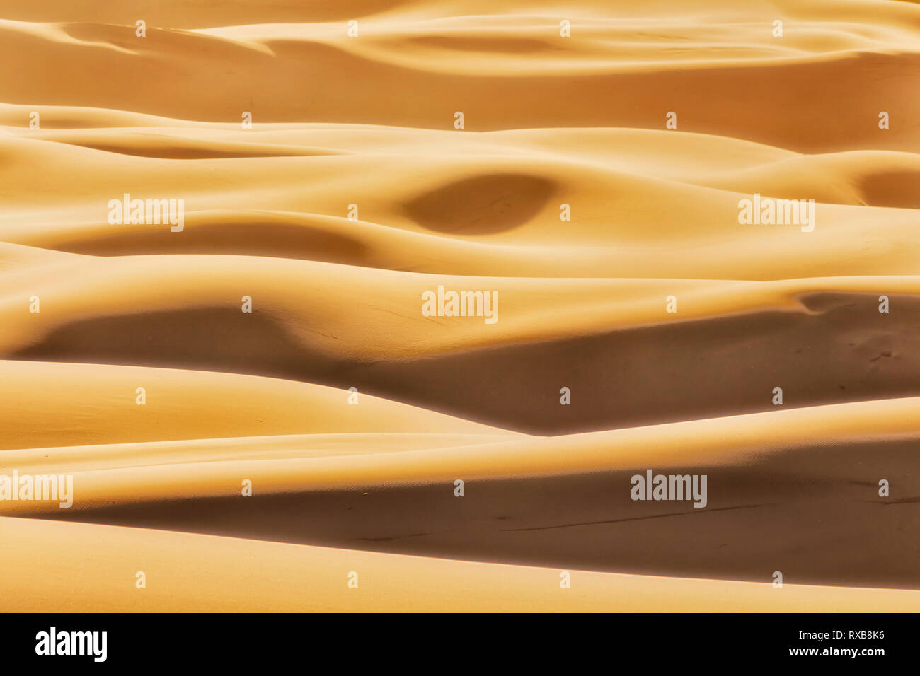 Simple shapes formed by sun light and shades on endless waves of sand dunes in arid lifeless desert of Australian Pacific coast at Stockton beach. - Stock Image