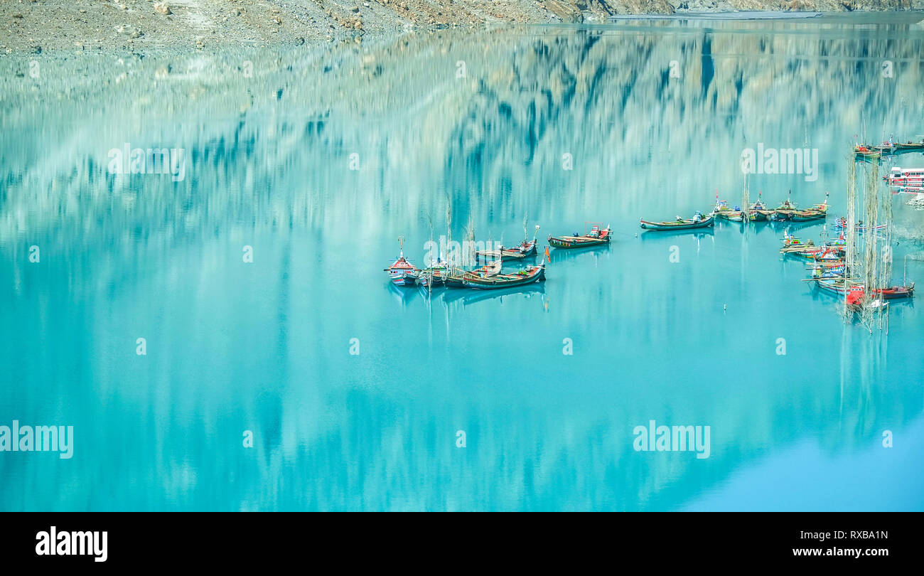Docked boats in the turquoise Attabad lake with reflection of mountain. Gojal Hunza. Gilgit Baltistan, Pakistan. - Stock Image