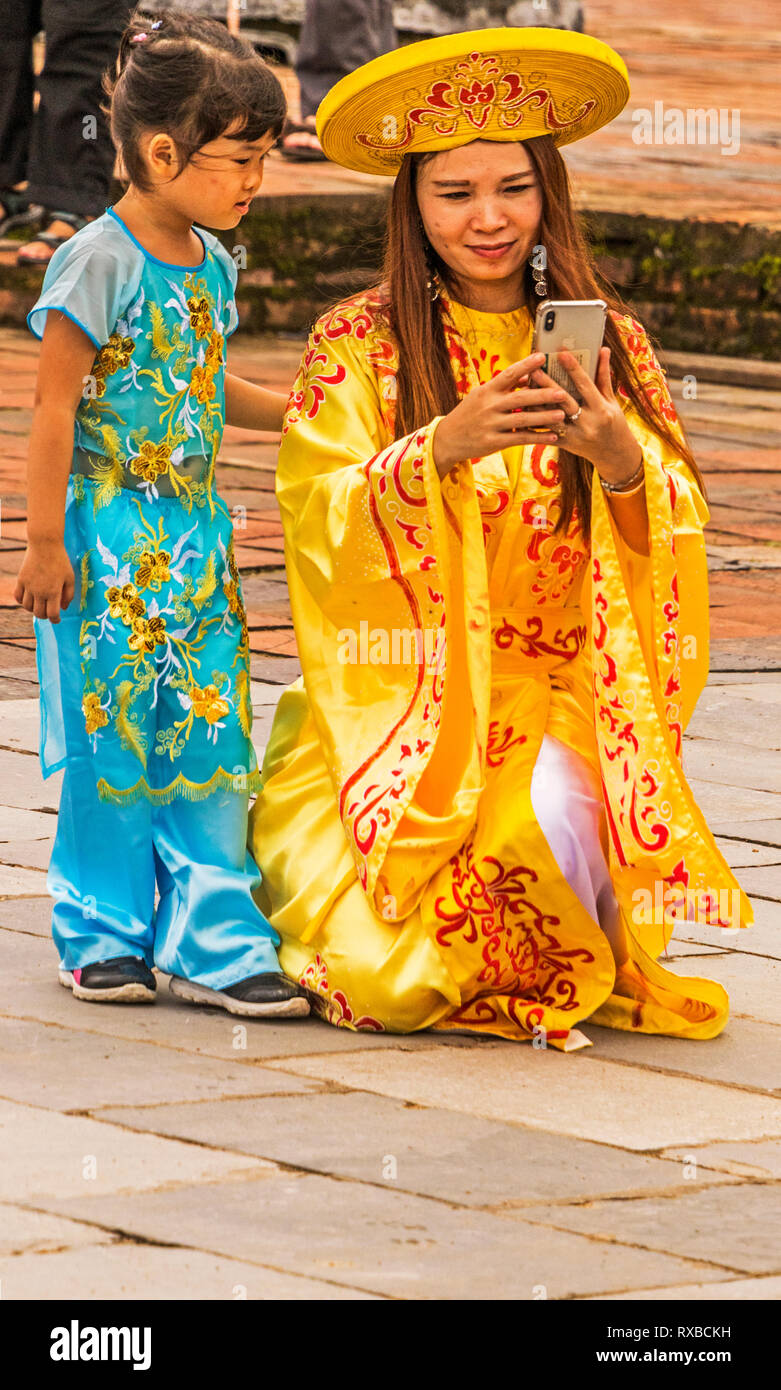 Visitors dress up in Vietnamese royal regalia in Hue's historical Imperial city Vietnam - Stock Image