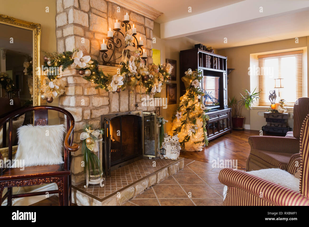 Antique wooden and two upholstered sitting chairs in front of natural cut-stone wood burning fireplace with Christmas decorations in living room insid - Stock Image