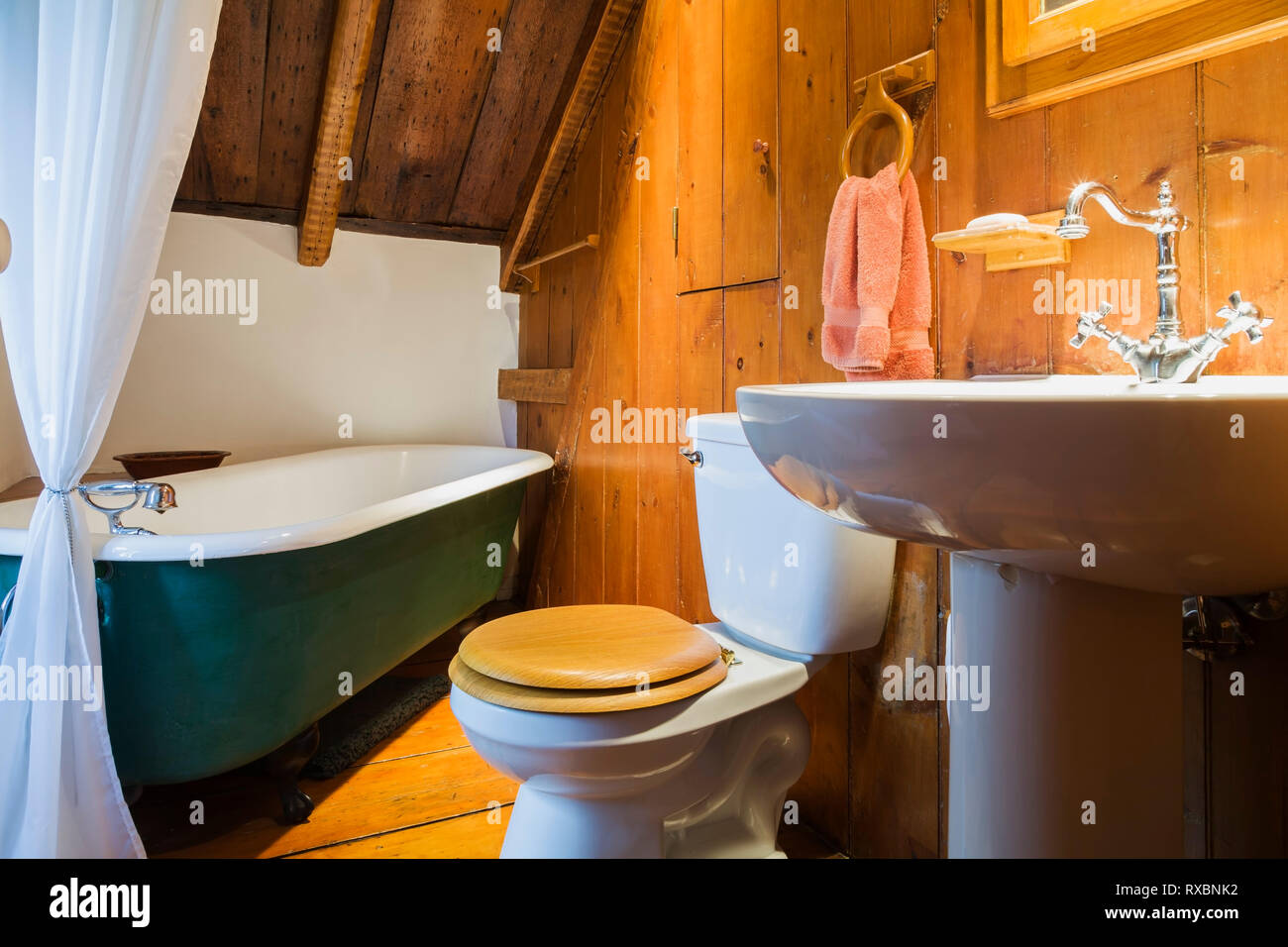 Bathroom with green 1880s claw-foot soaking tub on the upstairs floor inside an old circa 1750 Canadiana style fieldstone house, Quebec, Canada. This  - Stock Image