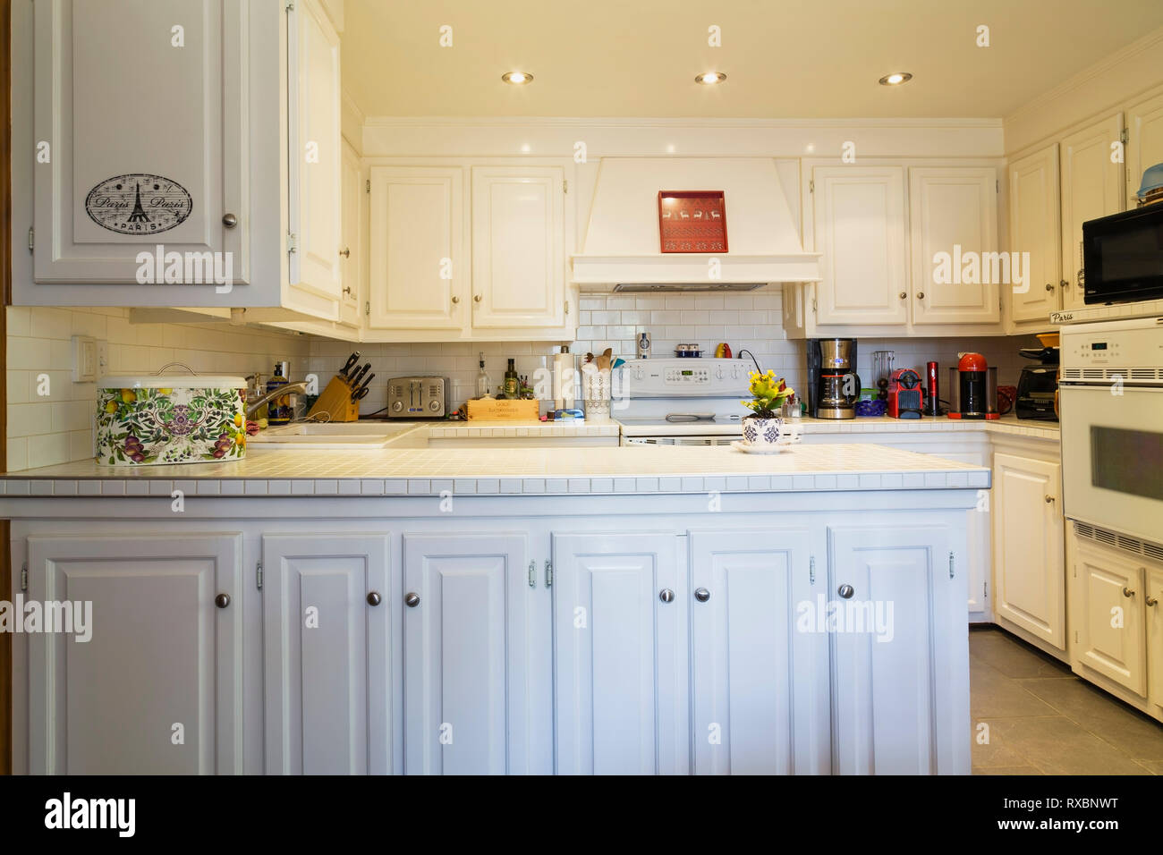 Country style kitchen with white cabinets and ceramic tile ...