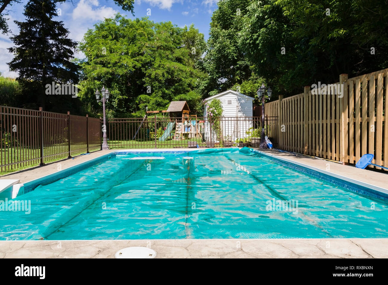 In-ground rectangular swimming pool with protective green ...