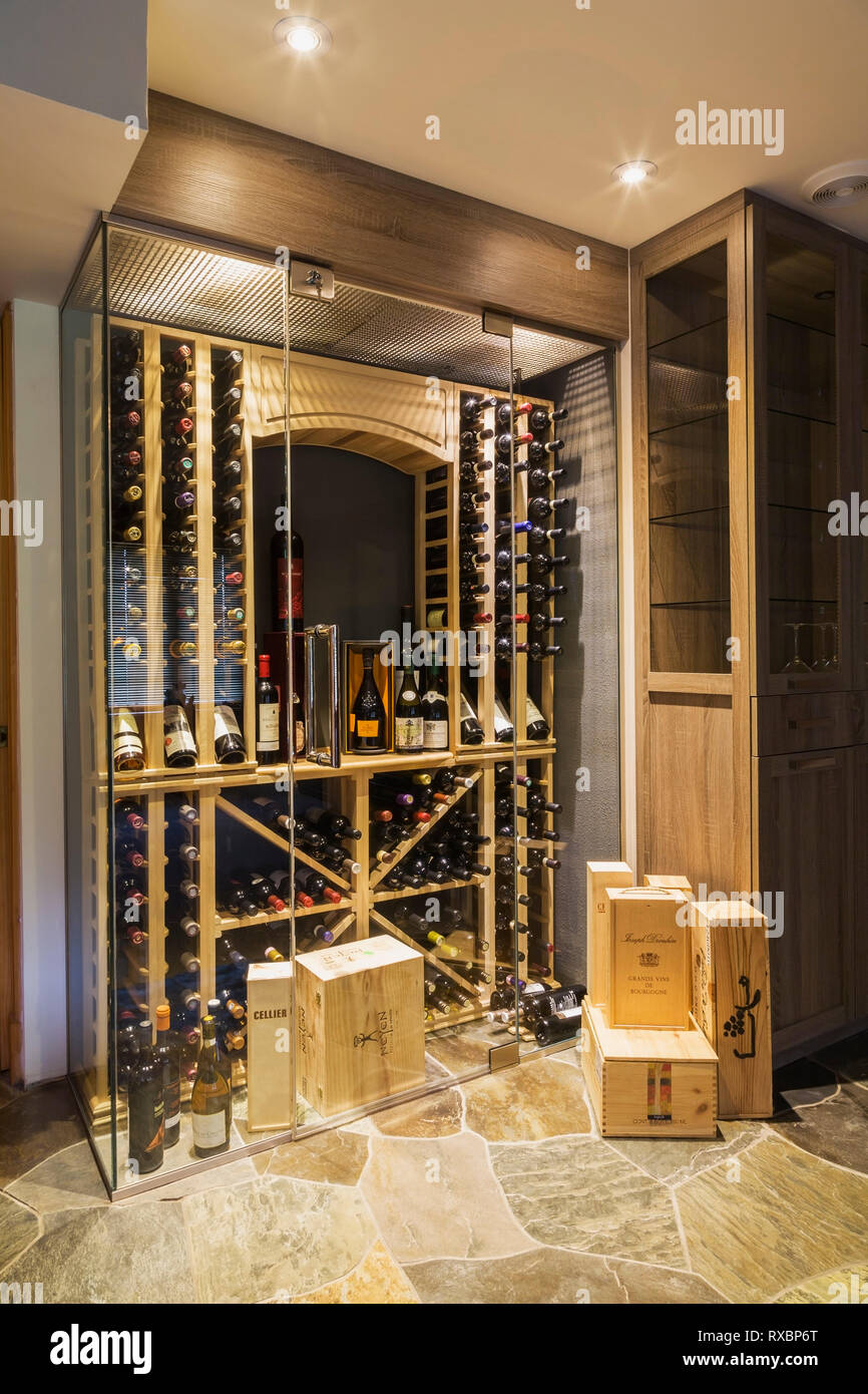 Illuninated Clear Glass Enclosed Wine Cellar With Wooden Shelves And Racks Filled With Bottles In Basement With Slate Tile Floor Inside A Piece Sur Piece Eastern White Pine Log And Timber Home