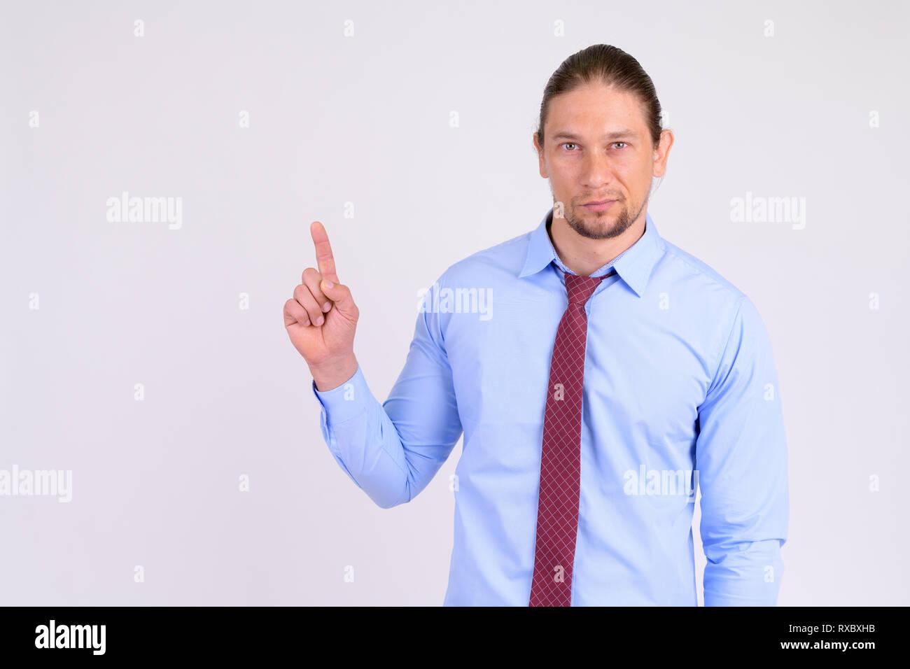Portrait of handsome businessman pointing finger up - Stock Image