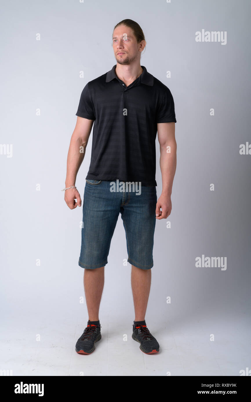 Full body shot of handsome man thinking and looking up - Stock Image
