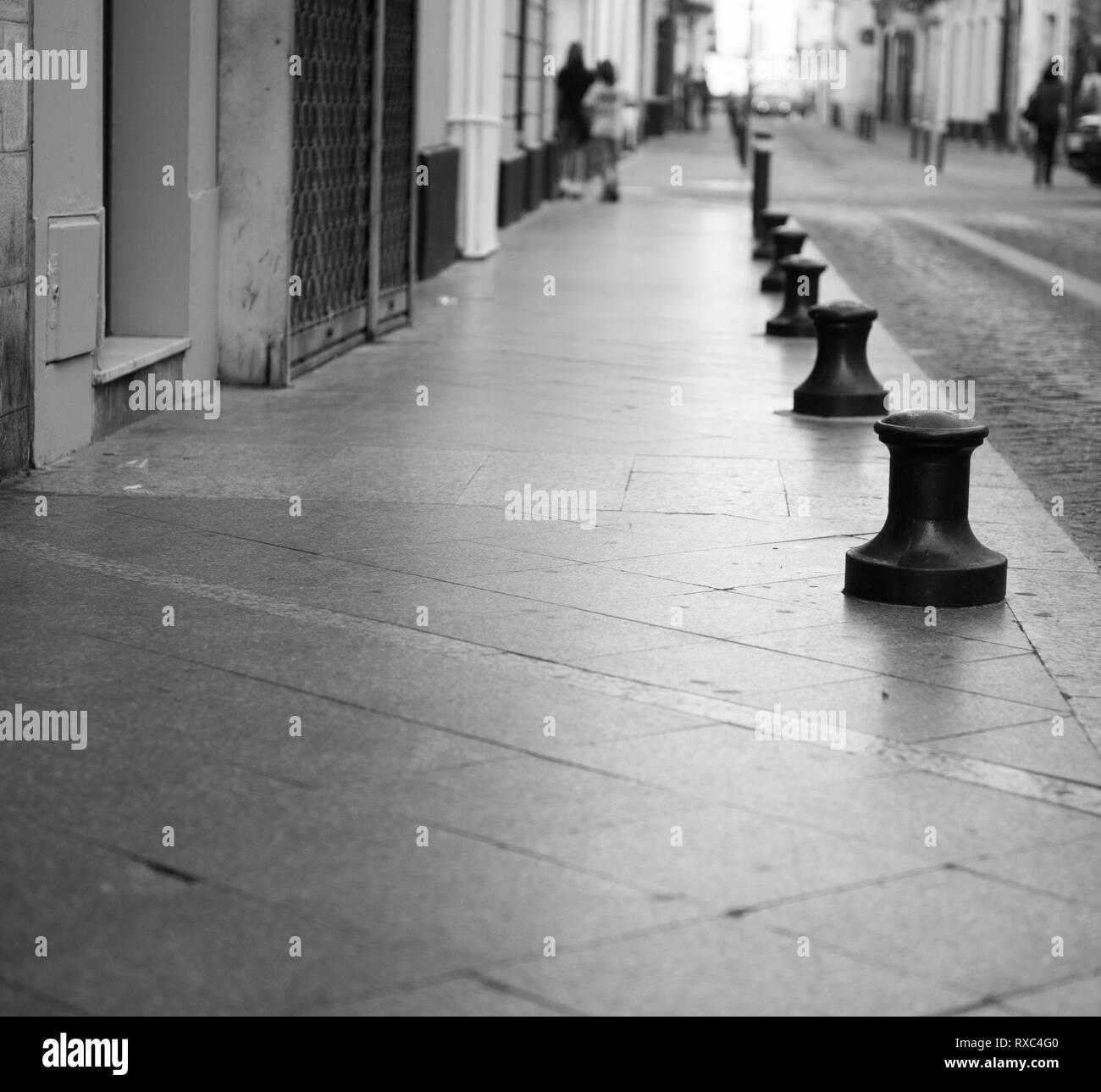 Line of metal bollards marking the pavement edge in an empty street.   distant unidentifiable figure add scale, Street furniture bollard - Stock Image