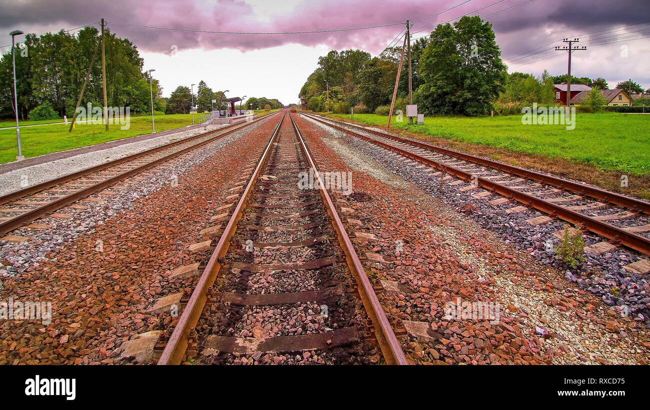 The rail tracks on the side of the green fields. With lots of stones this is where the train will pass by - Stock Image