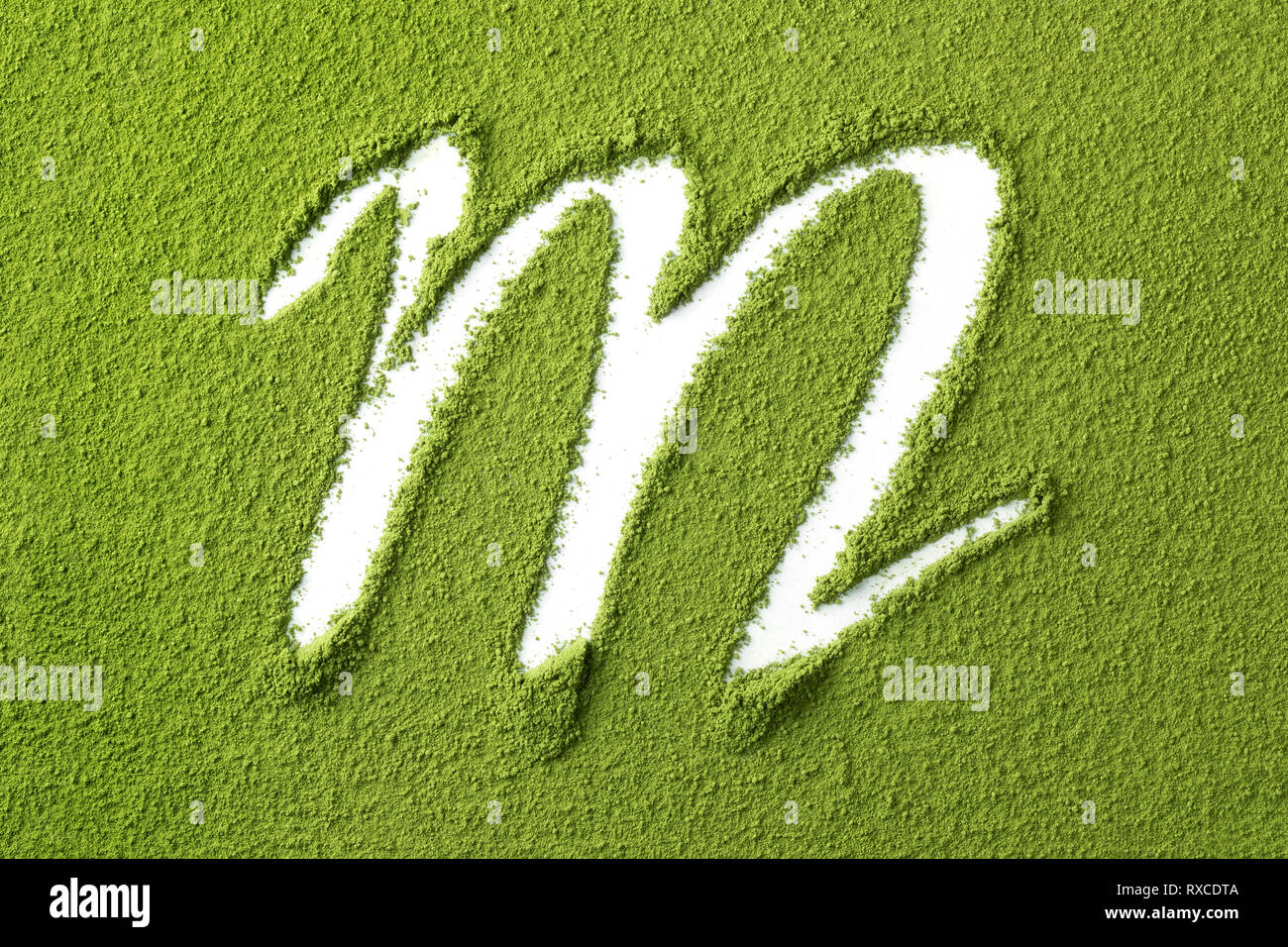 Green Japanese Matcha tea powder full frame and the letter M close up - Stock Image