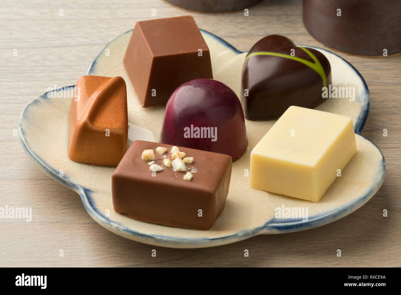 Dish with assorted chocolate bonbons for dessert - Stock Image