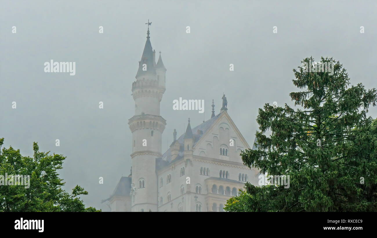 The Neuschwanstein castle on a hill in Germany. Neuschwanstein Castle is a nineteenth-century Romanesque Revival palace on a rugged hill above the vil - Stock Image