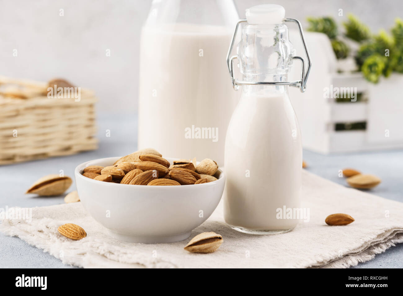 Homemade nut milk in bottles and raw almonds. Milk substitute. - Stock Image
