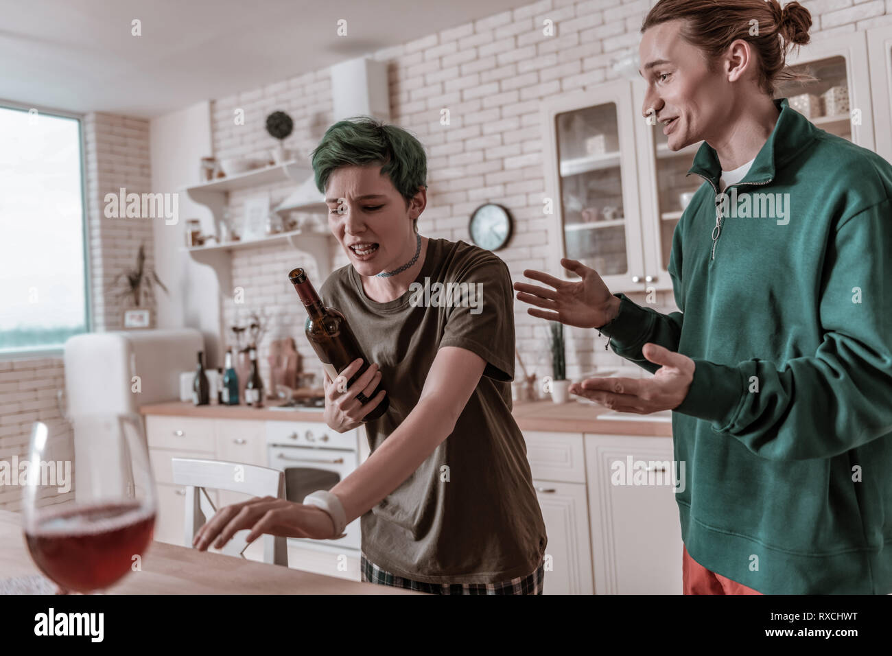 Hysterical green-haired woman crying and holding bottle of wine - Stock Image