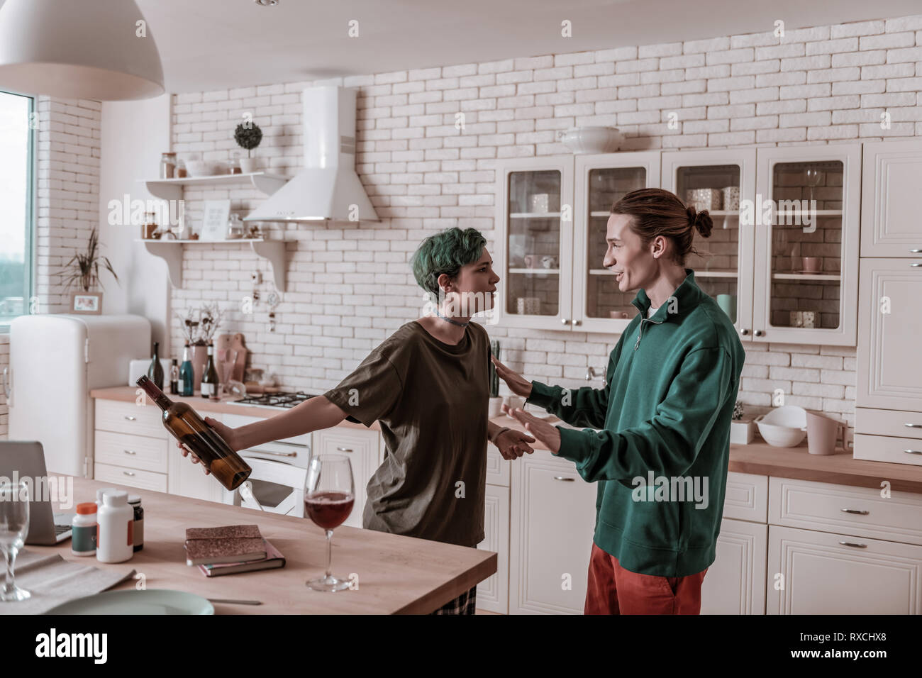 Wife holding bottle of wine after drinking on her own Stock Photo