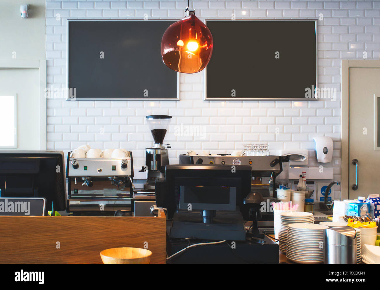 Counter top at a bright cafe with empty blackboards on the wall for copy space - Stock Image