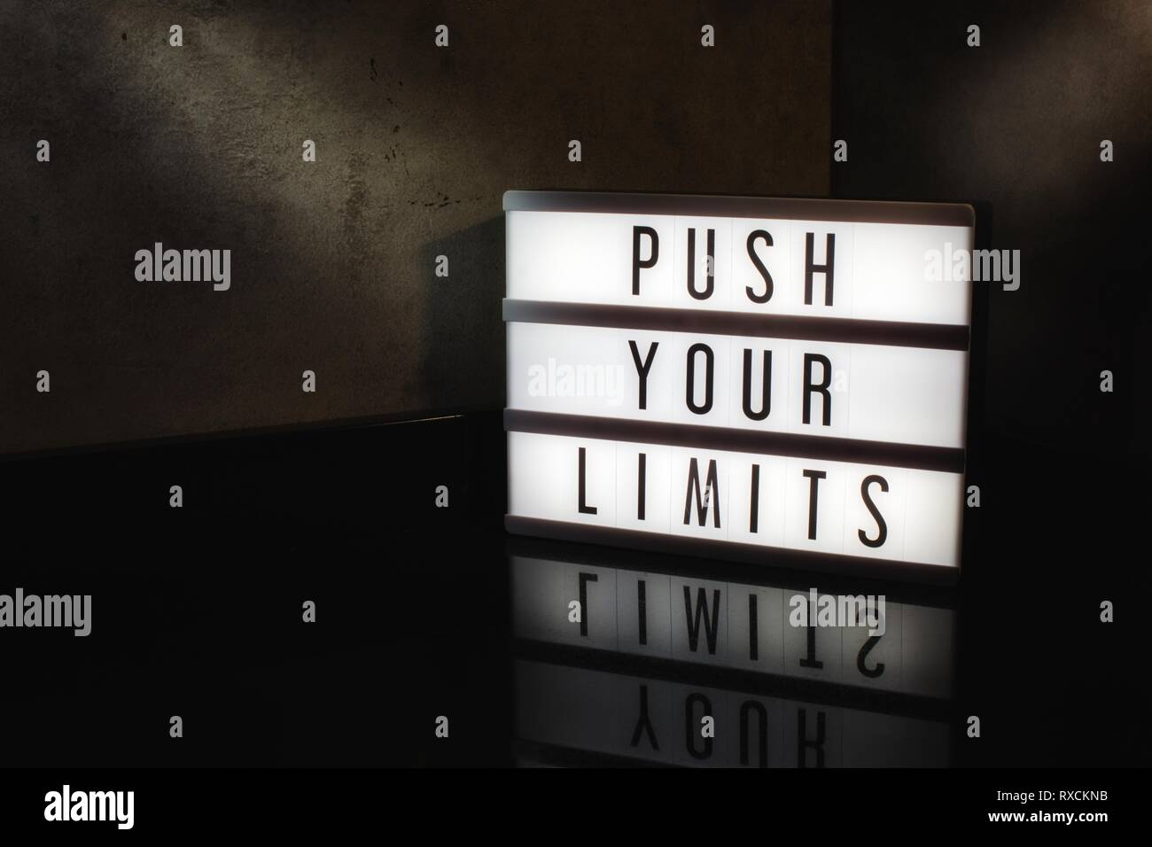 Push your limits motivational message on a light box in a cinematic moody background - Stock Image