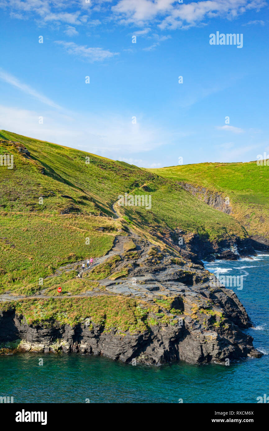 2 July 2018: Boscastle, Cornwall, UK - The South West Coast Path on the cliff tops near Boscastle, as a group of people walk down toward the harbour. Stock Photo