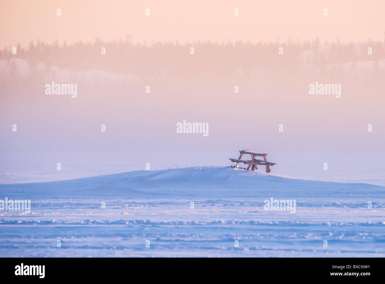 A picnic table surrounded by deep snow at sunrise on a frozen Great Slave Lake in Yellowknife, Northwest Territories, Canada. - Stock Image
