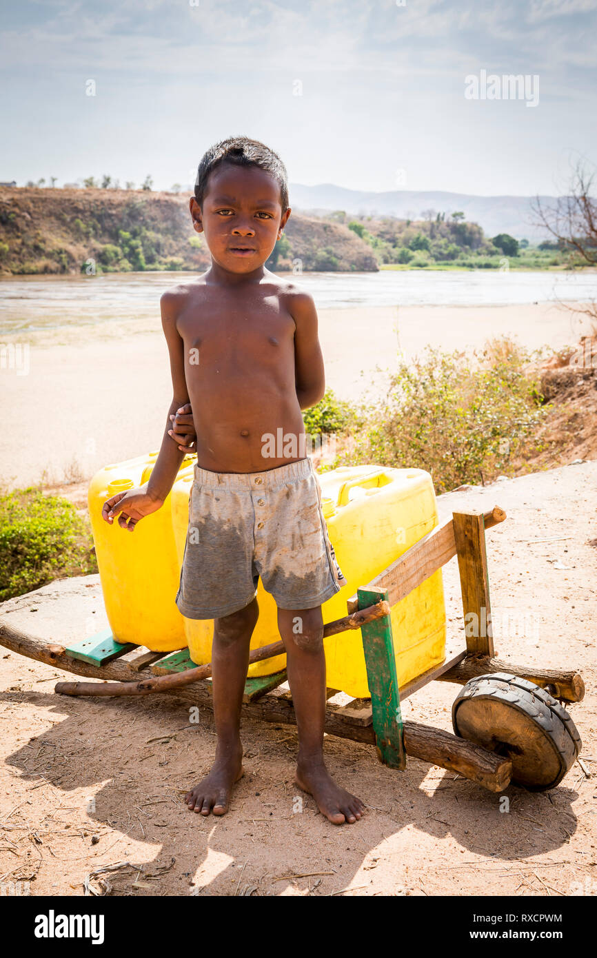 Water supply. Child working in the distribution of water in Containers, Morondava, Madagascar - Stock Image