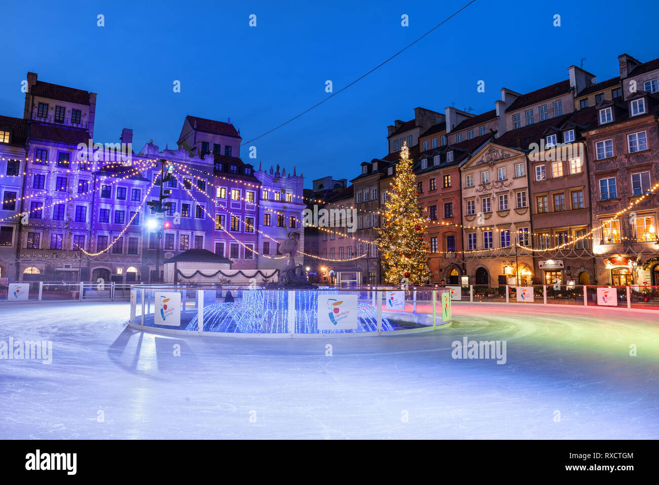 Ice skating rink on Old Town Square in Warsaw at night during Christmas time, capital city of Poland. - Stock Image