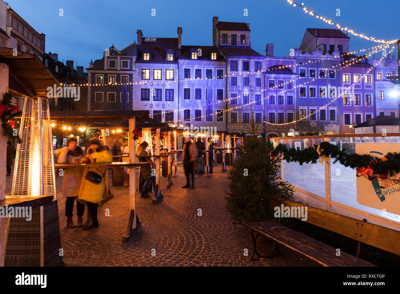 Poland, city of Warsaw, people enjoy their beverages at Old Town Market Square on winter night during Christmas time. - Stock Image