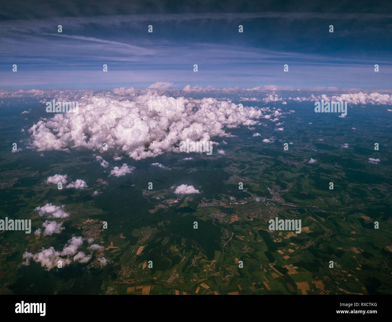 View of clouds, green landscape and cities out of aircraft window Stock Photo