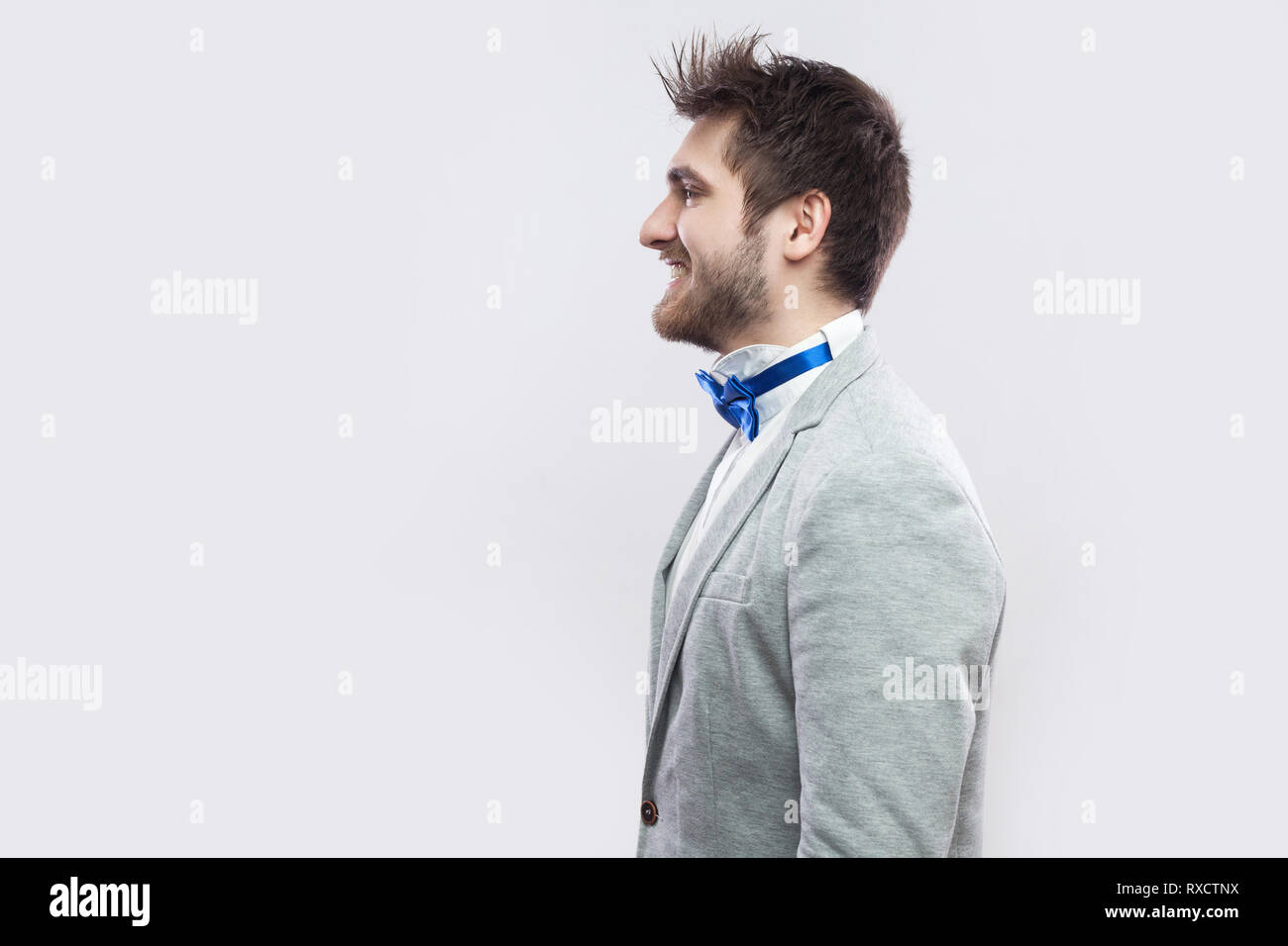 f7c22175995f Profile side view portrait of happy satisfied handsome bearded man in casual  grey suit and blue