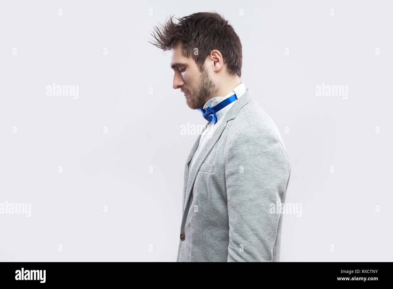 99699adcce10 Profile side view portrait of alone handsome bearded man in casual grey suit  and blue bow