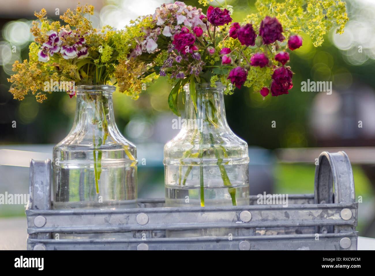 Blumengesteck in einer Glasflasche im Zink-Behälter. Lila Blumen - Stock Image