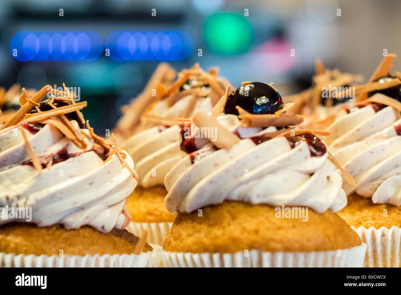 Sahnehäubchen mit Kirsche, feine Süßspeisen aus Mutters Küche - Stock Image
