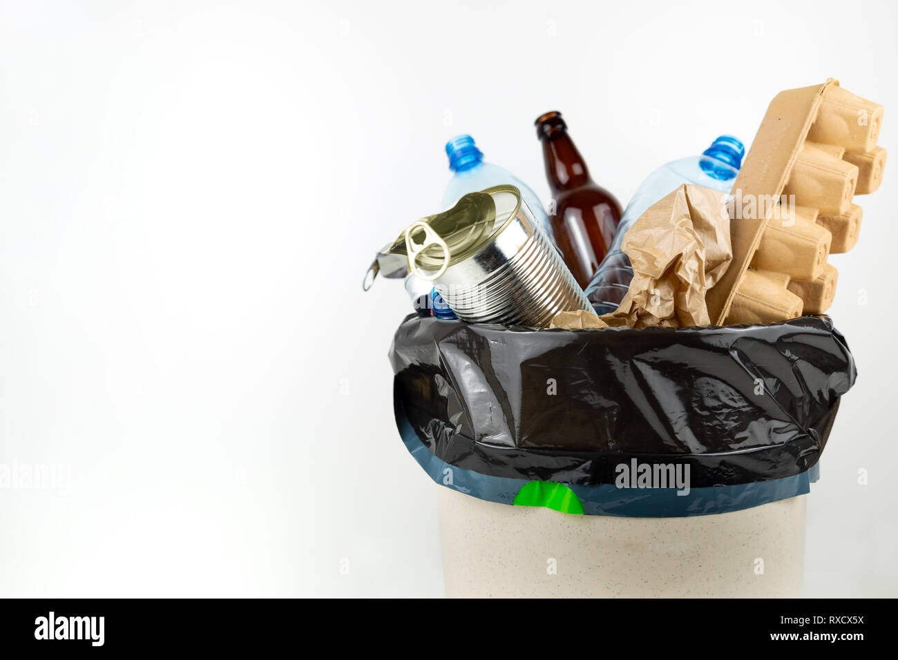 Plastic, glass, metal and paper garbage in black garbage bag for recycling concept reuse and recycle - Stock Image
