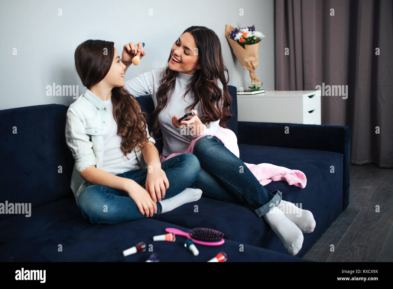 Beautiful brunette caucasian mother and daughter sit together in room. Mom does make up for girl. She use powder and brush. Hairbrush and nail polish Stock Photo