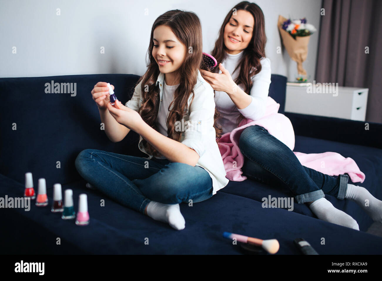 Beautiful brunette caucasian mother and daughter sit together in room. Girl use nail polish and smile. Young woman brush daughter hair. Beauty session Stock Photo