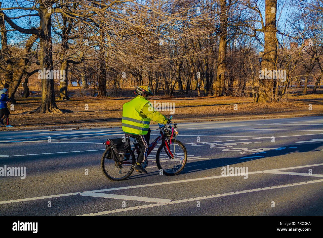 Man wearing Green vest riding bicycle on the Prospect Park road in Brooklyn New York, February - Stock Image