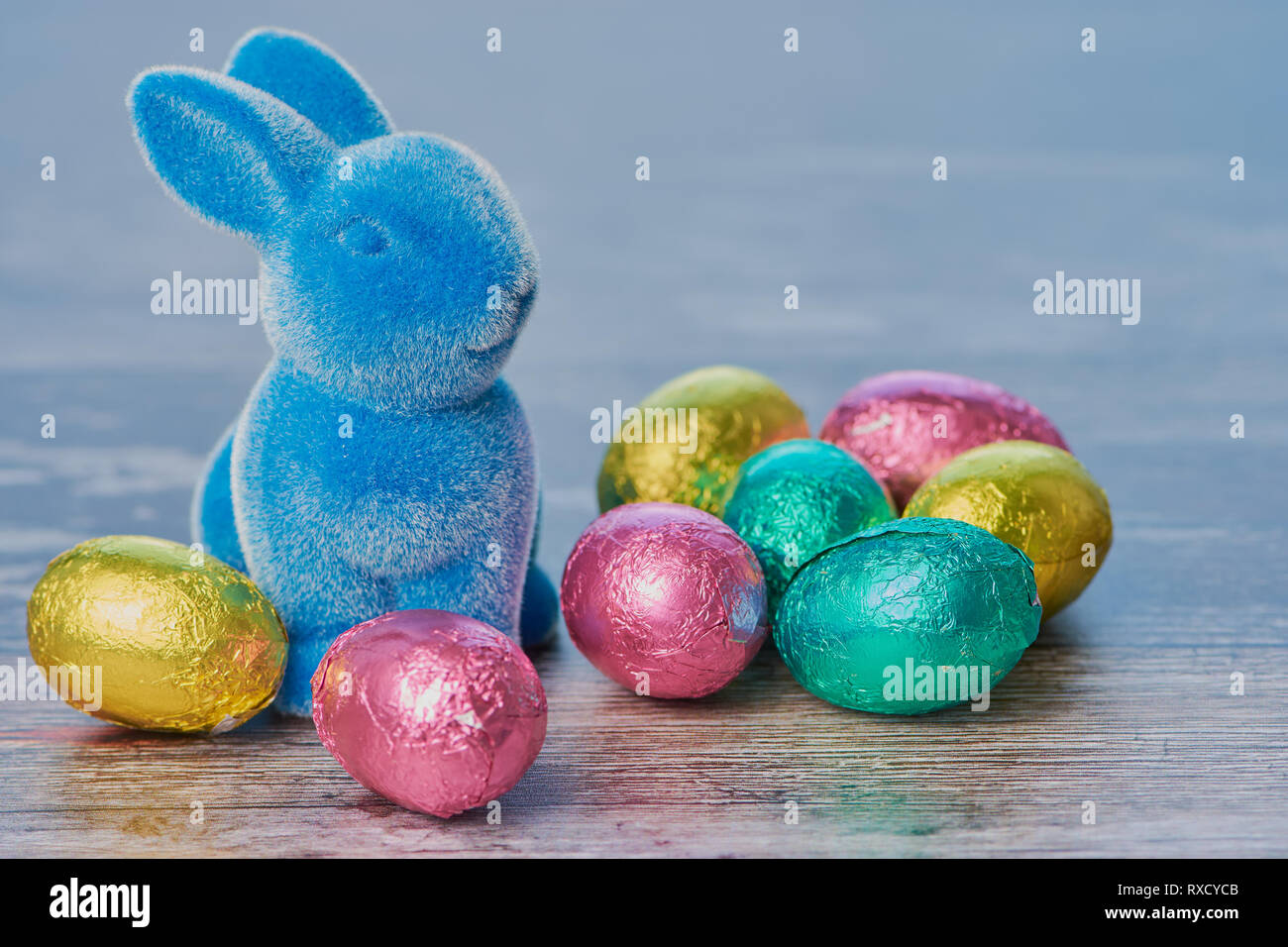 blue easter bunny with wrapped chocolate eggs against white wooden background with copy space Stock Photo