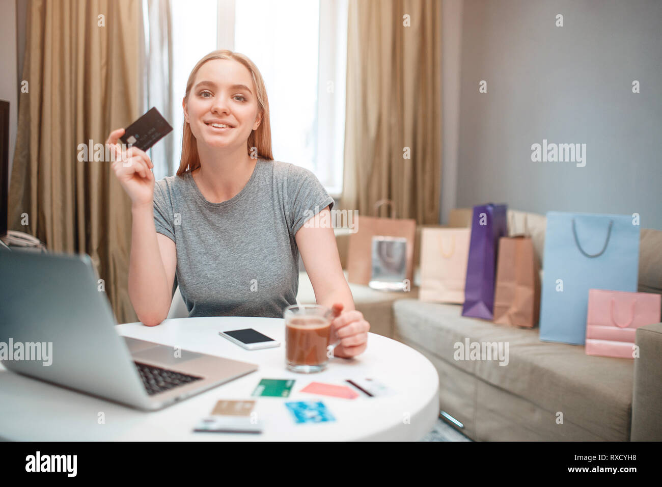 Online shopping at home. Young happy woman is ready to spend money from payment card on black Friday while sitting at the table - Stock Image