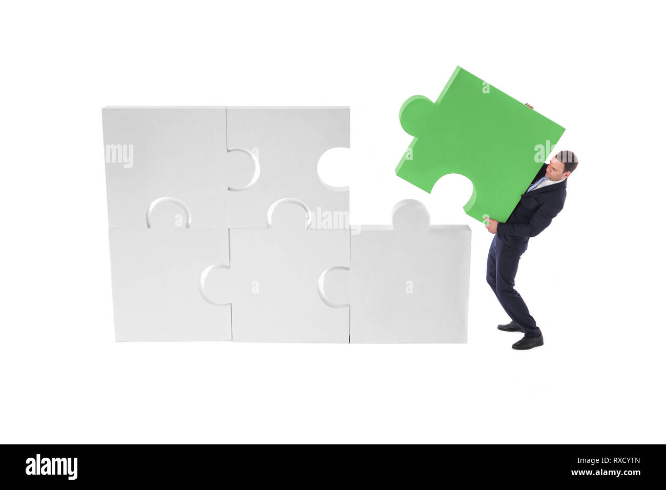 Business man assembling puzzle of giant pieces . Strategy and problem solution concept - Stock Image