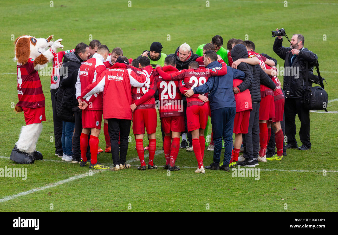 sports, football, Regional League West, 2018/2019, Rot Weiss Oberhausen vs Bonner SC 01/04 4-0, Stadium Niederrhein in Oberhausen, players, coaches, helpers and mascot Underdog of Oberhausen building a circle, team spirit, solidarity, invocation - Stock Image