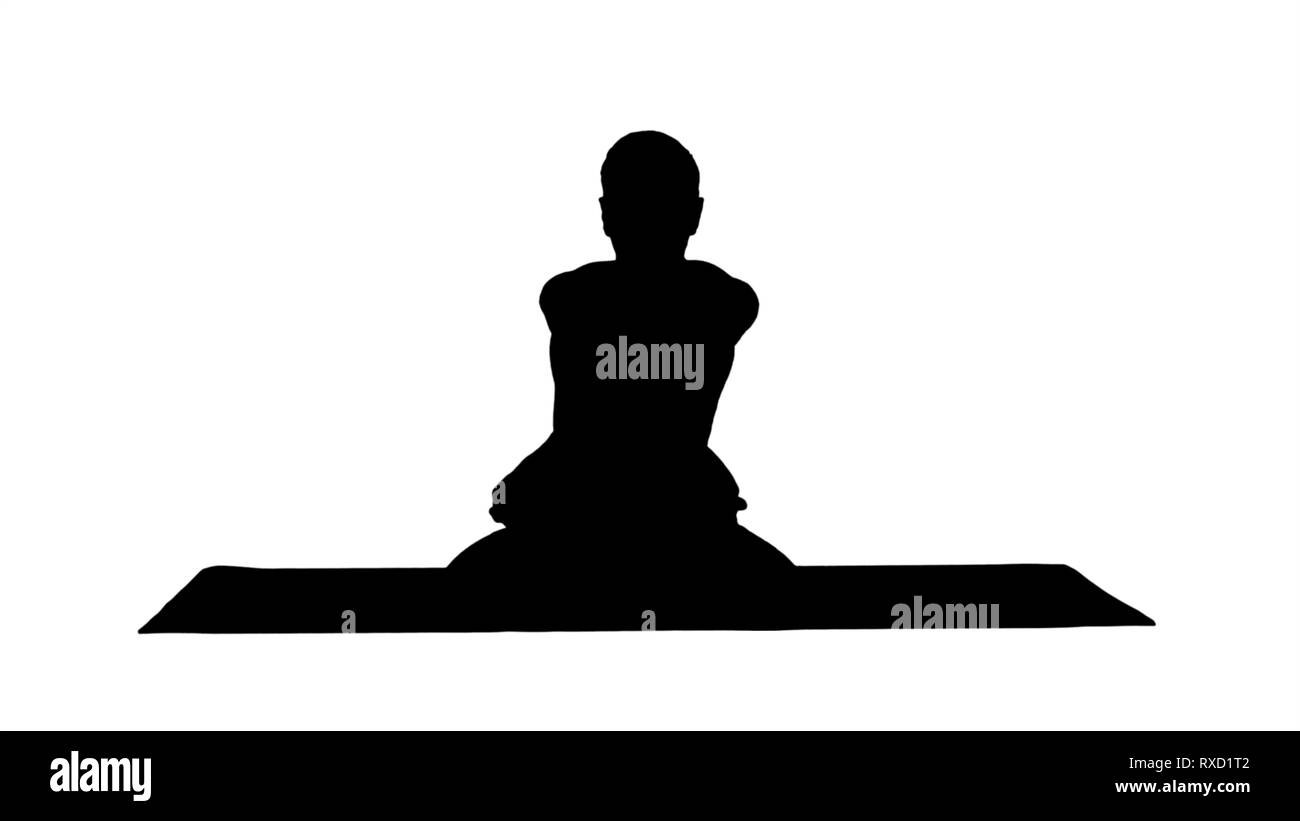 Silhouette Sporty beautiful young man practicing yoga, sitting cross-legged in Adho Mukha Padmasana, bending forward in variation of Lotus Pose. - Stock Image
