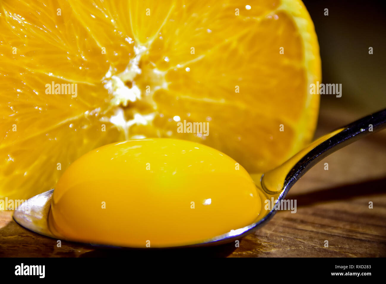 close-up of an egg yoke in a silver spoon in front of an orange sliced in a half - Stock Image