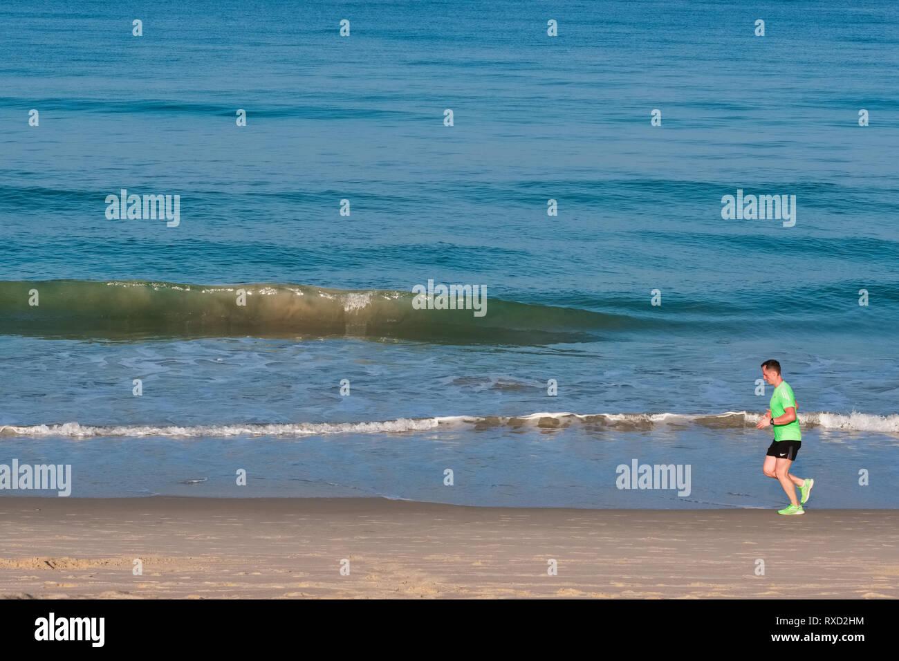 On an early morning at Bang Tao Beach, Phuket, Thailand, a jogger runs along the shoreline - Stock Image