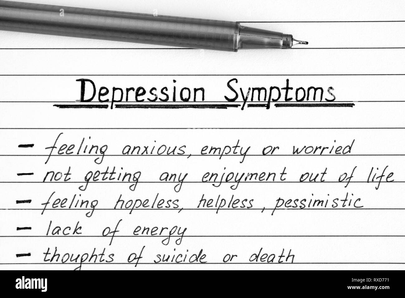 Depression Symptoms writing on the list  with pen. Close-up. - Stock Image