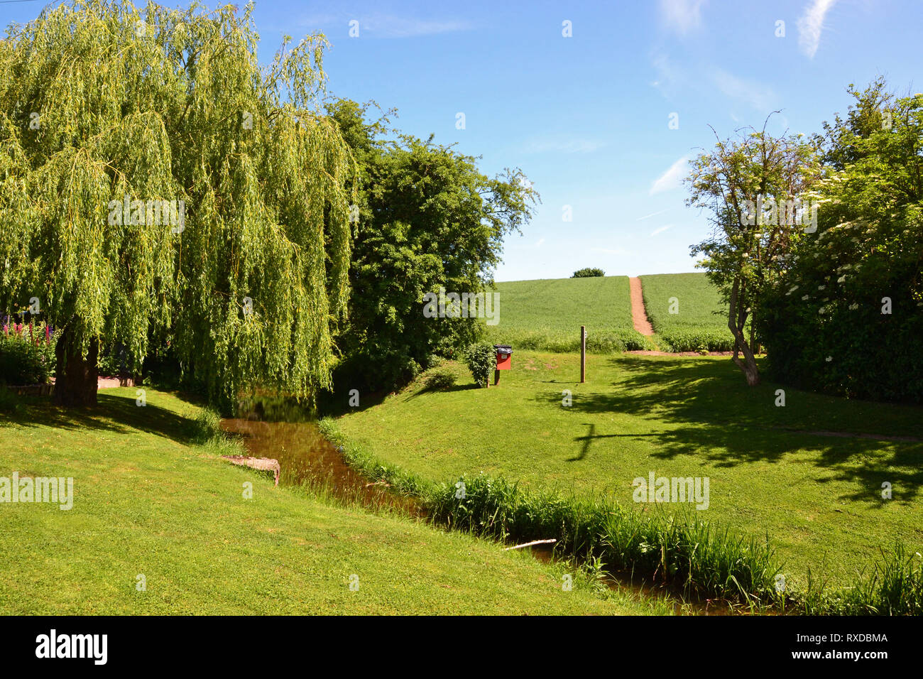 Pretty recreation ground / park with a stream running through it, on the egde of Lavenham town in Suffolk, UK. Sunny day. - Stock Image